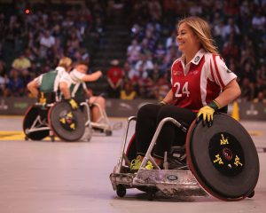 Accessibility: Young woman in sports wheelchair playing basketball