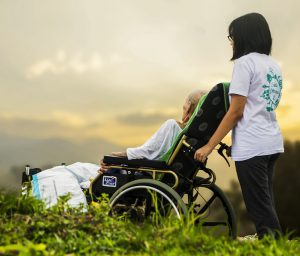 Accessibility - helper pushes old lady in wheelchair