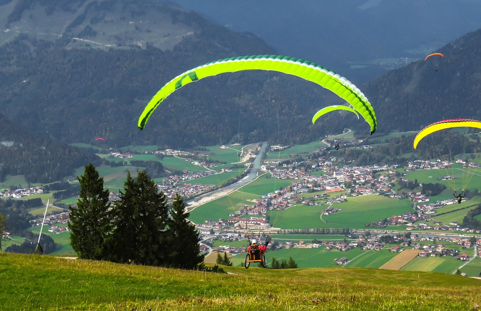 paraglider in a wheelchair, who just started off into a wide valley