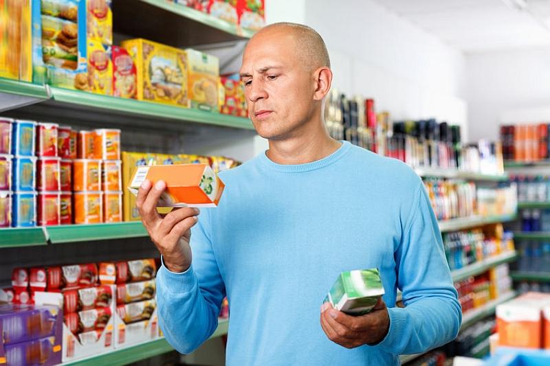 Mann im Supermarkt liest mühsam Etiketten