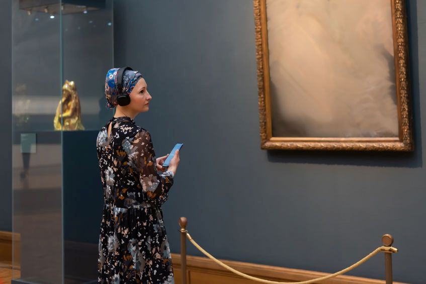 Junge Frau in Museum mit Audio Guide