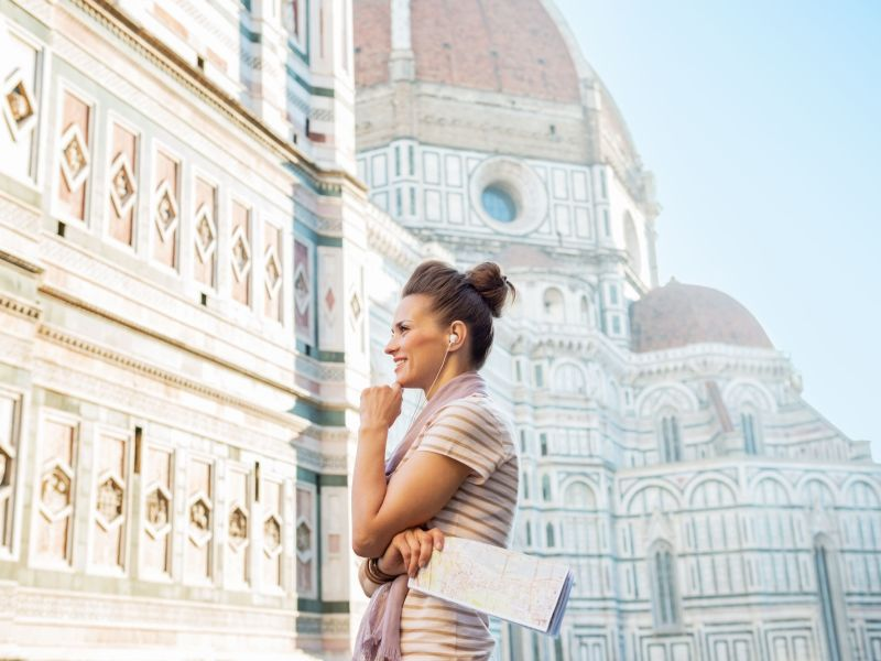 young, smiling woman with earsets, looking at the dome in Florence on a sunny summer day - she enjoys the audio messages of voice marketing