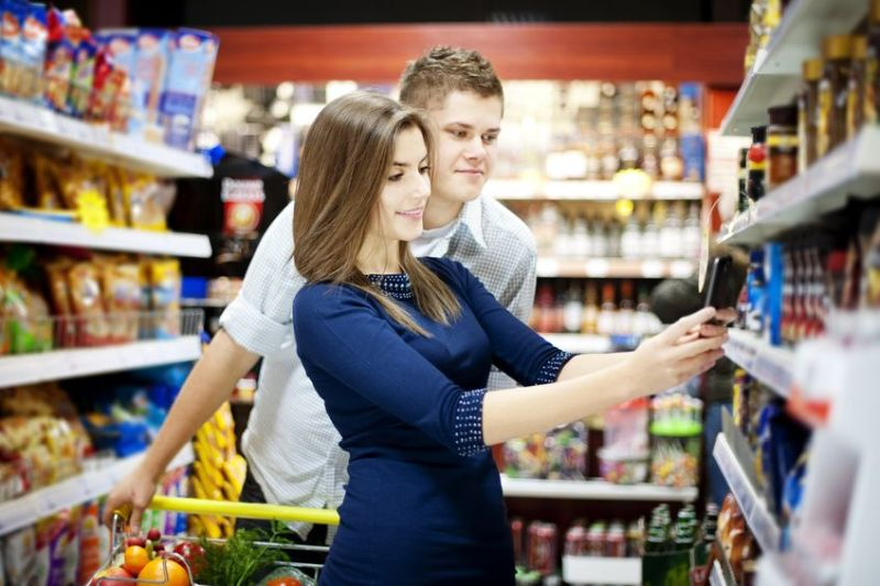 Smart Packaging: The picture shows a smiling young couple in a supermarket. The woman in a blue dress is scanning a product on the shelf, while the man is watching.