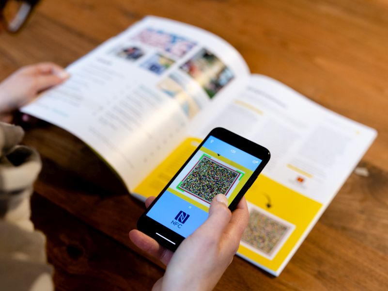 Person scanning a speech code from a magazine