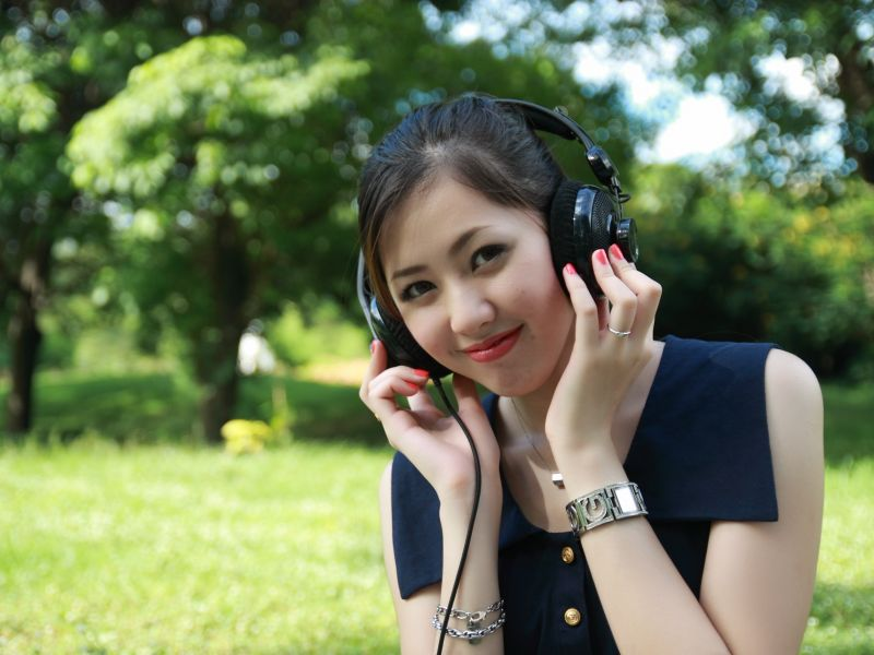 Smiling girl with headphones in a park