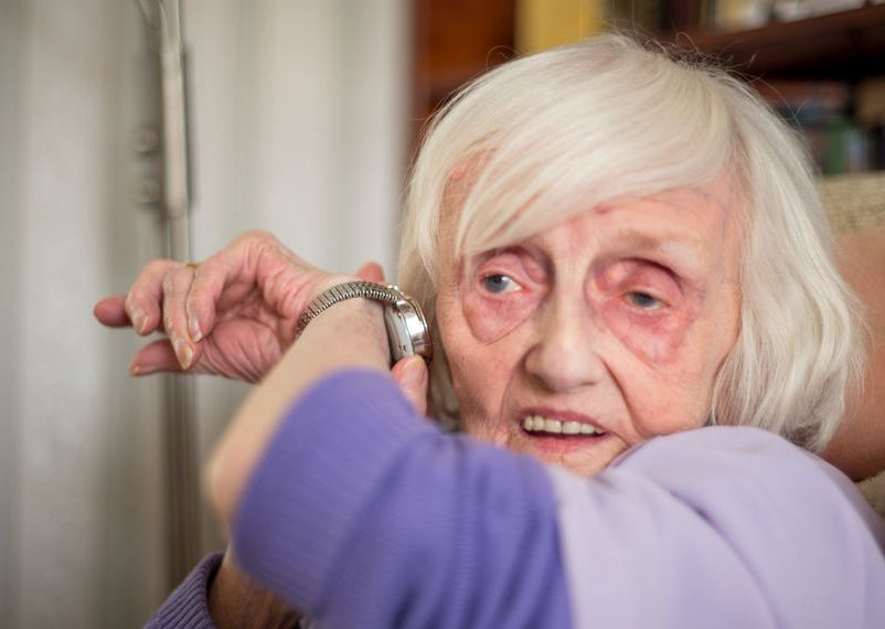 Aids for visual impairment: lind,elderly woman listening to her talking wrist watch