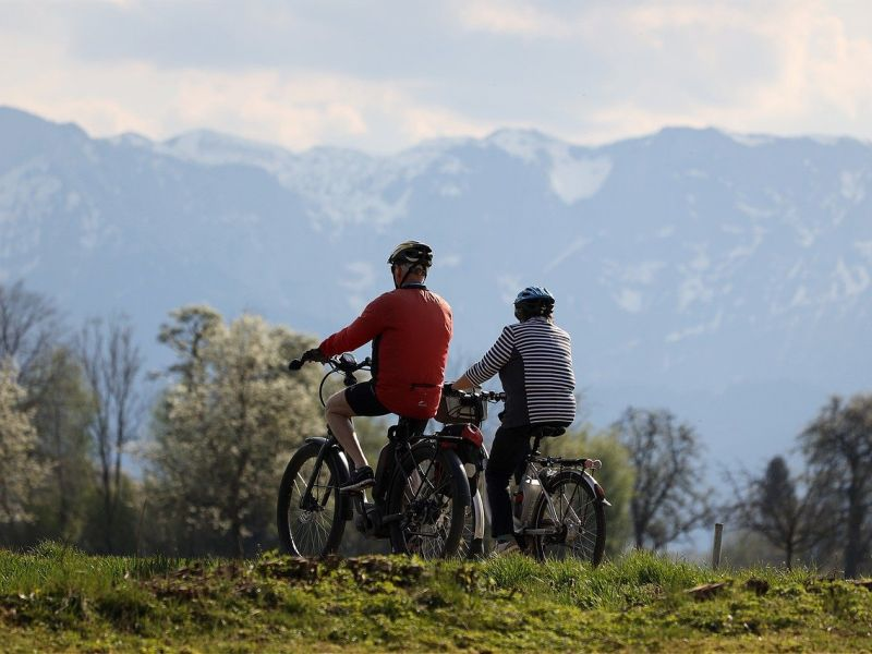 Sustainable tourism in the great outdoors: an elderly couple in sportswear riding IeBikes in a meadow. In front of them are flowering trees, in the distance high mountains still covered with remnants of snow.