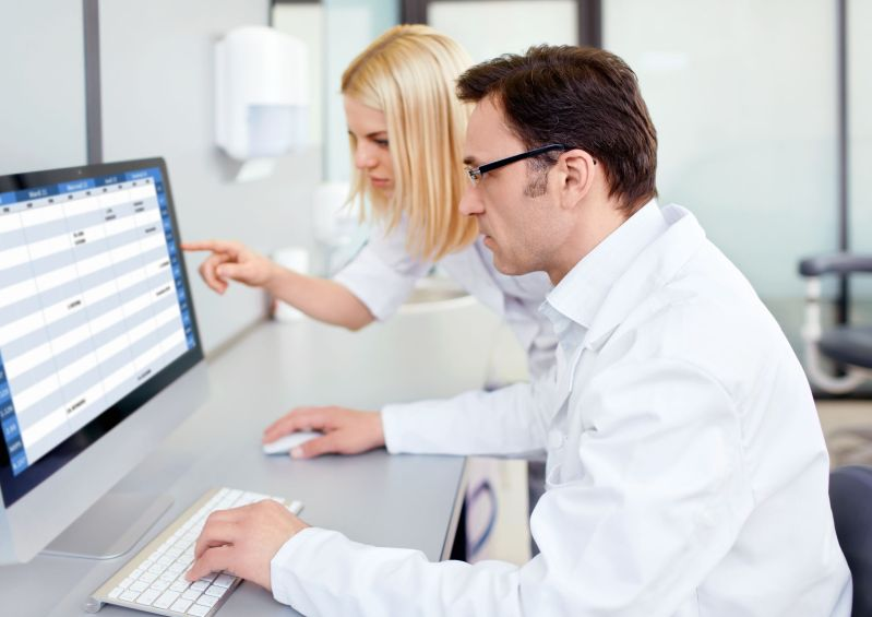 Man and woman in laboratory clothing look at computer screen