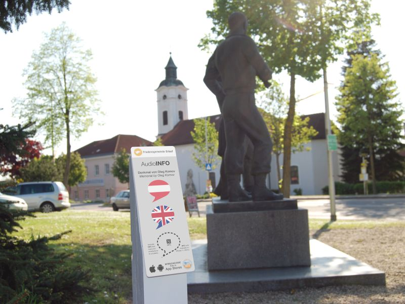 Small sign with SpeechCode Audio Info at a WW 2 memorial in a village square. In the background is the church and museume und Museum.