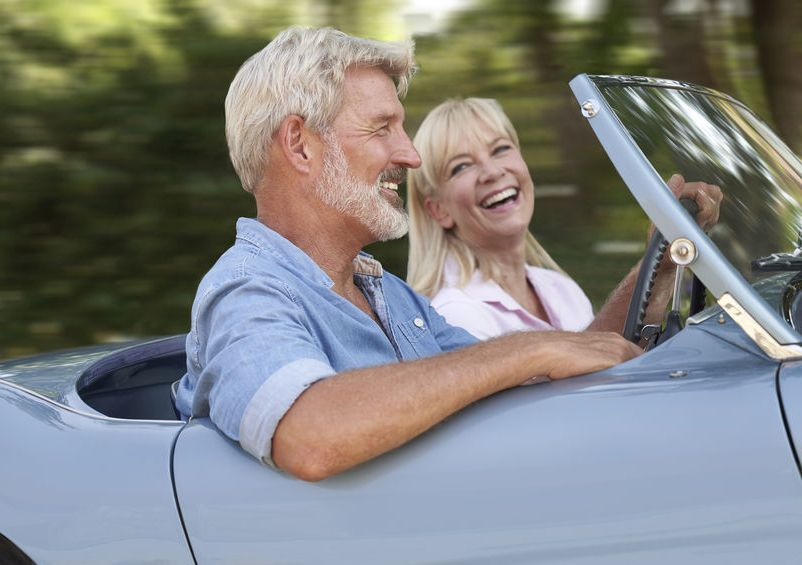 Generation 50+ - happy middle aged couple driving a convertible