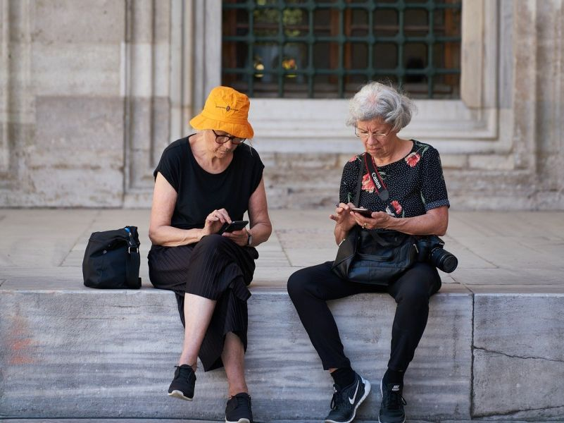 2 old ladies in black leisure clothes and sneakers. They are sitting on a wall during sightseeing and are busy with their smartphones.