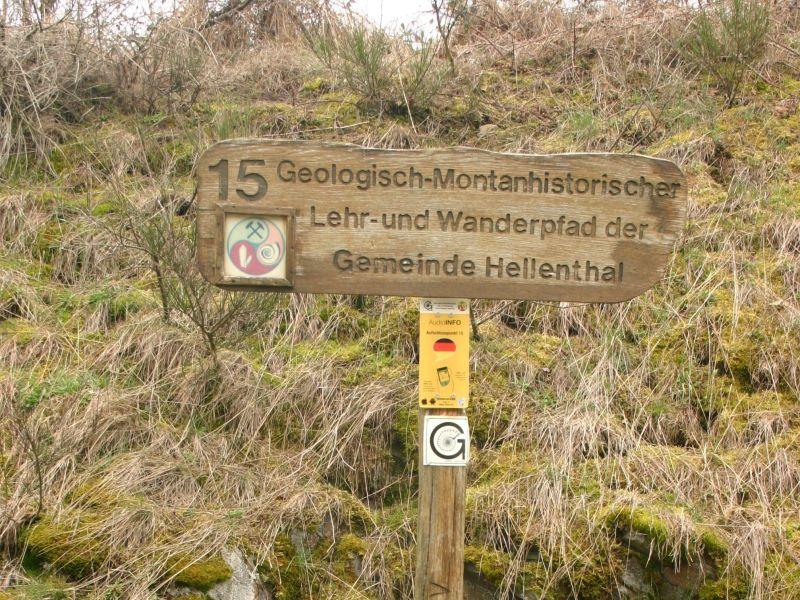 """Themenweg Holztafel mit der Aufschrift """"Geologisch Montan historischer Lehr- und Wanderpfad der Gemeinde Hellenthal"""". Darunter ist ein 10 mal 30 Zentimeter kleines Schild """"Audio Info"""""""