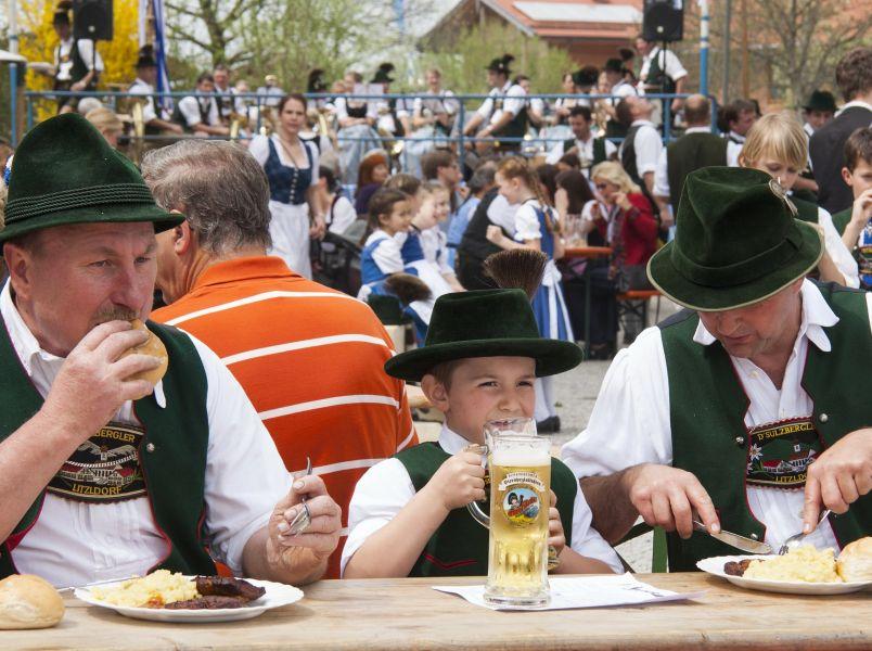 2 Männer und ein Junge essen an Holztisch beim Dorffest