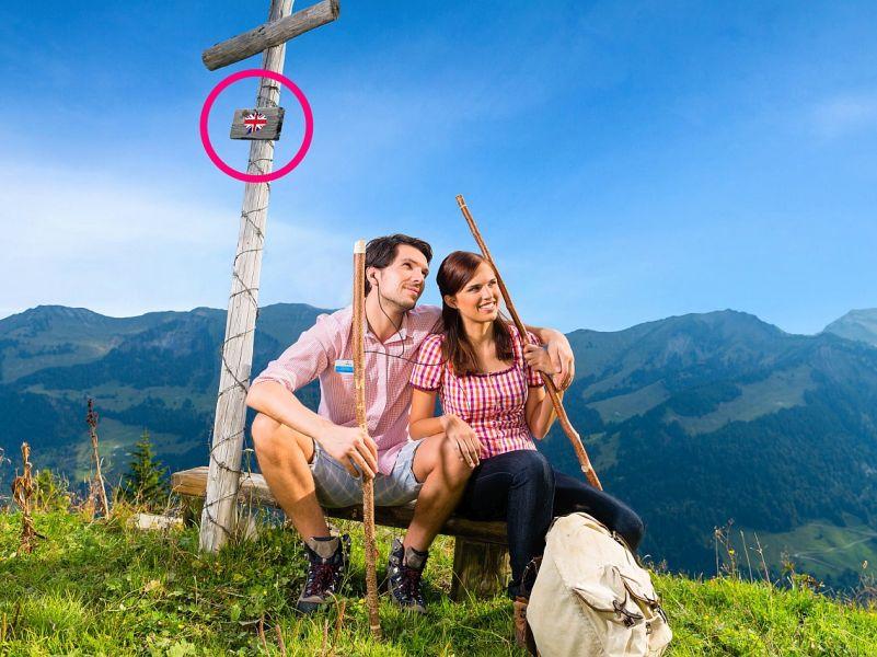 Lächelndes, junges Paar auf Gipfel mit Ohrhörern